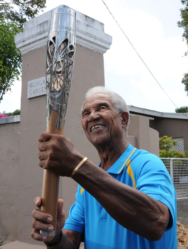 National hero and cricketing legend, Sir Garfield Sobers, proudly holding the baton